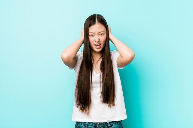 Jonge vrij chinese vrouw die oren behandelt met handen die niet te hard geluid proberen te horen.