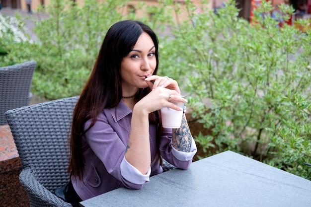 Jonge vrij donkerbruine vrouw die melkachtige cocktail drinkt