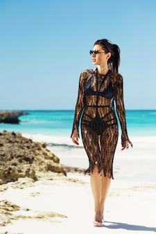 Jonge vrij hete sexy vrouw op het tropische eiland in de zomer in de buurt van de zee en de blauwe hemel. meisje in zonnebril loopt langs het strand.
