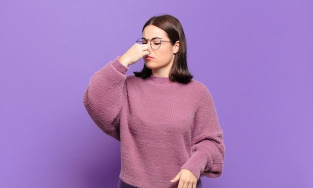 Jonge, vrij informele vrouw die walgt, neus vasthoudt om te voorkomen dat ze een vieze en onaangename stank ruikt