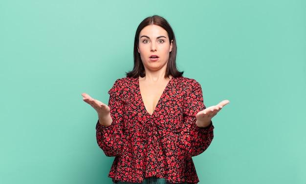 Jonge, vrij informele vrouw die zich extreem geschokt en verrast, angstig en in paniek voelt, met een gestreste en geschokte blik