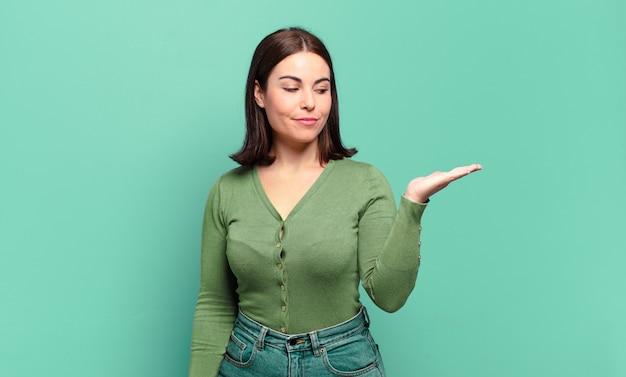 Jonge, vrij informele vrouw die zich gelukkig voelt en terloops lacht, op zoek naar een object of concept dat aan de zijkant wordt vastgehouden