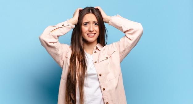 Jonge, vrij informele vrouw die zich gestrest, bezorgd, angstig of bang voelt, met de handen op het hoofd, in paniek raakt bij vergissing