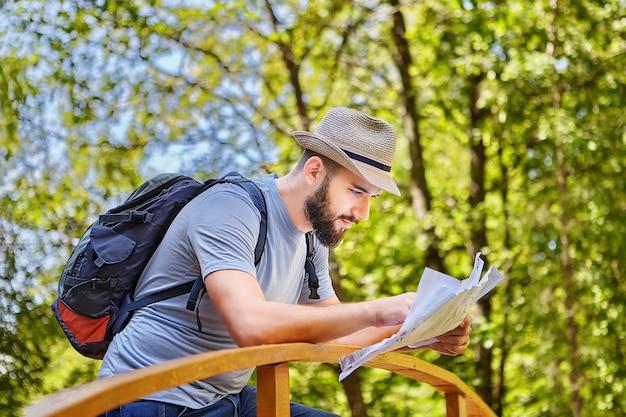 Jonge vrij kaukasische backpacker controleert kaart van zijn route die op brug in bos is.