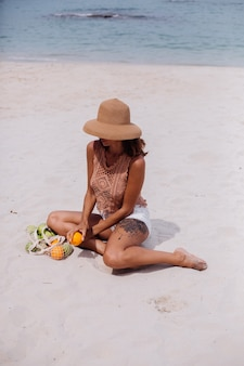 Jonge vrij kaukasische gelooide geschikte vrouw in gebreide kleding en hoed op strand