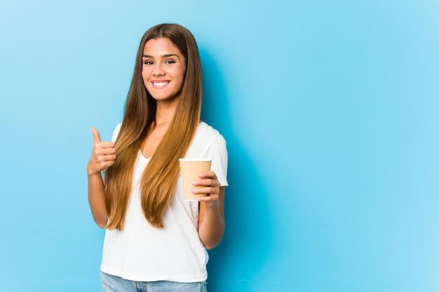 Jonge vrij kaukasische vrouw die een meeneemkoffie houdt glimlachend en duim opheffend