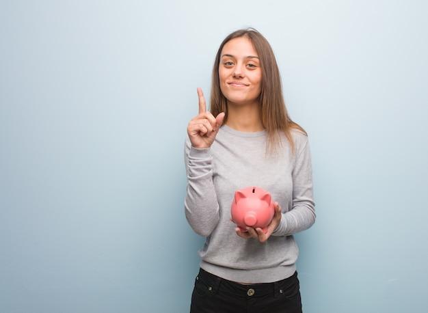 Jonge vrij kaukasische vrouw die nummer één toont. ze houdt een spaarvarken vast.