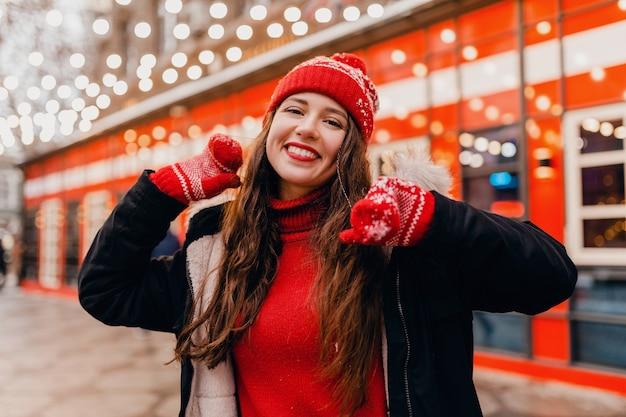 Jonge vrij lachende gelukkige vrouw in rode wanten en gebreide muts dragen winterjas wandelen in de stad straat, warme kleren
