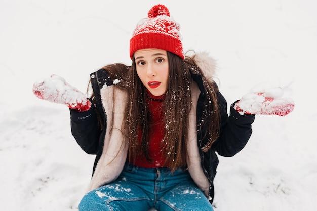 Jonge vrij lachende gelukkige vrouw in rode wanten en gebreide muts dragen winterjas, wandelen in het park, spelen met sneeuw in warme kleren