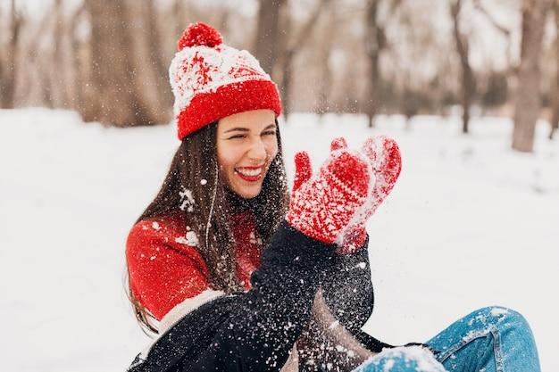 Jonge vrij lachende gelukkige vrouw in rode wanten en gebreide muts dragen winterjas zittend op sneeuw in park, warme kleren