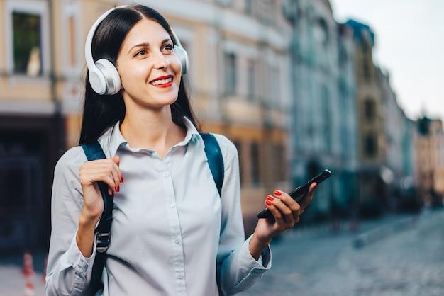 Jonge vrij langharige toeristenvrouw met een rugzak die van de wandeling door de oude stadsstraat geniet en naar muziek luistert