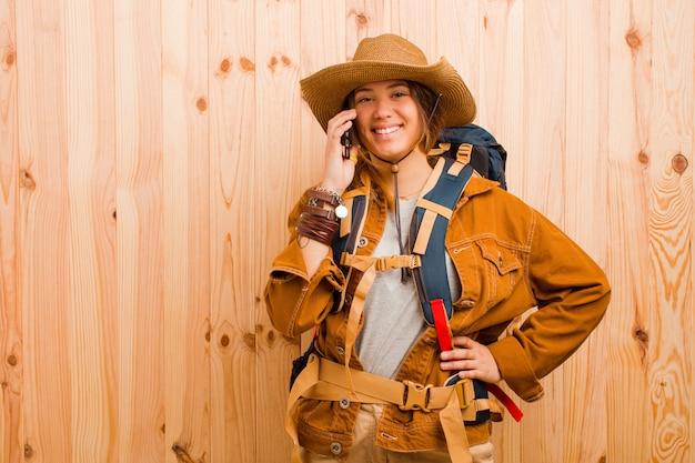 Jonge vrij latijnse reizigersvrouw tegen houten muur