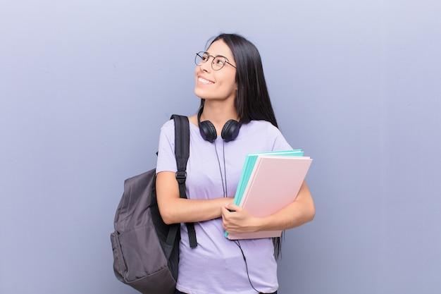 Jonge vrij latijnse studentenvrouw tegen grijze muur