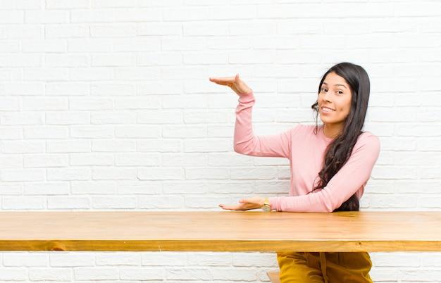 Jonge vrij latijnse vrouw die een voorwerp met beide handen aan kant copyspace houden, tonen die, een objectzitting voor een lijst aanbieden aanbieden