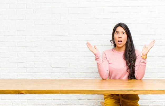 Jonge vrij latijnse vrouw die geschokt en verbaasd kijkt, met verbaasde mond van verbazing bij het realiseren van iets ongelooflijks dat voor een tafel zit