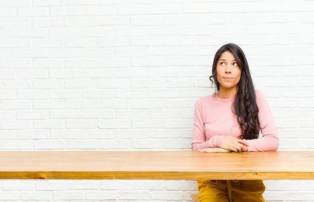 Jonge vrij latijnse vrouw die in verwarring gebracht en verward kijkt, een probleem benieuwd is of probeert op te lossen of denkt zittend voor een tafel