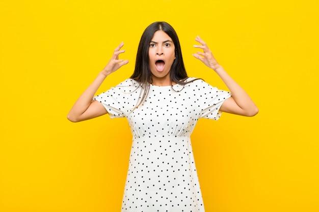 Jonge vrij latijnse vrouw die met handen omhoog in de lucht gilt, woedend, gefrustreerd, gestresst en overstuur voelt