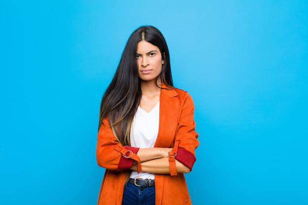 Jonge vrij latijnse vrouw die niet bevallen en teleurgesteld voelen, kijkend ernstig, geërgerd en boos met gekruiste wapens tegen vlakke muur