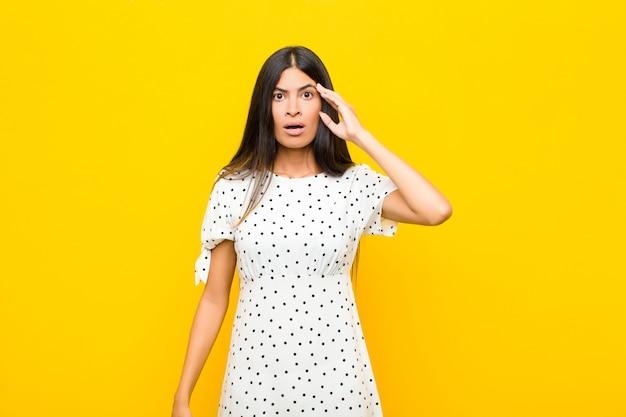 Jonge vrij latijnse vrouw die verrast, geschokt met open mond kijkt, realiserend een nieuwe gedachte, een idee of een concept tegen vlakke muur
