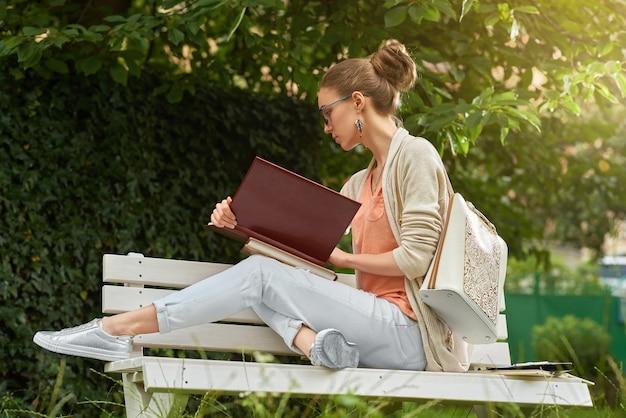 Jonge vrij modieuze vrouw die een boek op de bank in het park leest