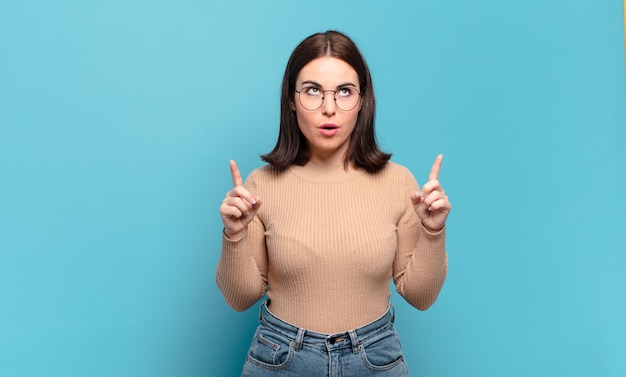 Jonge vrij ongedwongen vrouw die geschokt, verbaasd en met open mond kijkt, naar boven wijzend met beide handen om ruimte te kopiëren