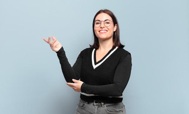 Jonge vrij ongedwongen vrouw die trots en zelfverzekerd glimlacht, zich gelukkig en tevreden voelt en een concept op exemplaarruimte toont