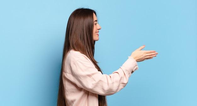 Jonge vrij ongedwongen vrouw die, u begroet en een handschudt aanbiedt om een succesvolle overeenkomst, samenwerkingsconcept te sluiten
