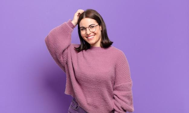 Jonge vrij ongedwongen vrouw die vrolijk en nonchalant glimlacht, hand aan hoofd neemt met een positieve, gelukkige en zelfverzekerde blik