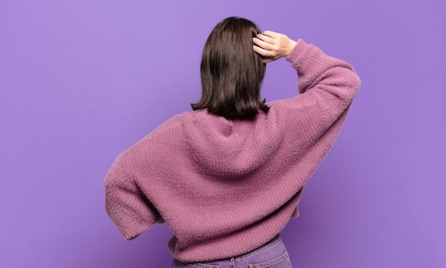 Jonge vrij ongedwongen vrouw die zich geen idee en verward voelt, een oplossing denkt, met de hand op de heup en de andere op het hoofd, achteraanzicht