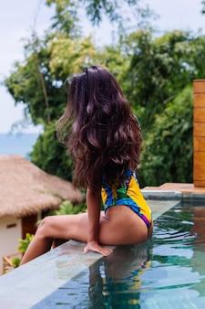 Jonge vrij positieve gelukkig slanke vrouw in kleurrijke zwembroek in geweldige luxe hotelvilla genieten van mooie dag op vakantie in thailand