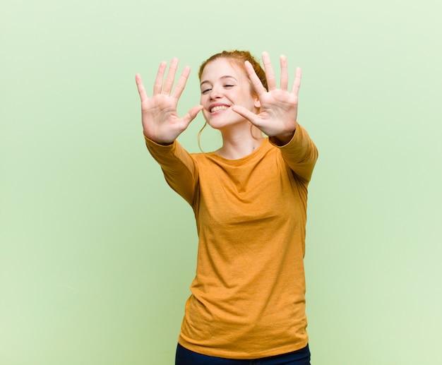 Jonge vrij rode hoofd en vrouw die vriendschappelijk glimlachen kijken, die nummer tien of tiende met vooruit hand tonen, die over groene muur aftellen