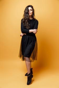 Jonge vrij sexy vrouw of meisje met schattig gezicht en lang donkerbruin haar heeft modieuze make-up in zwarte jurk op gele achtergrond