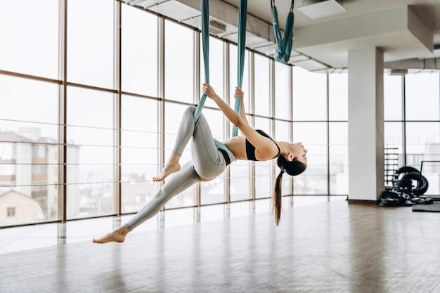 Jonge vrij slank lichaam fitness meisje het beoefenen van vlieg yoga in de sportschool.