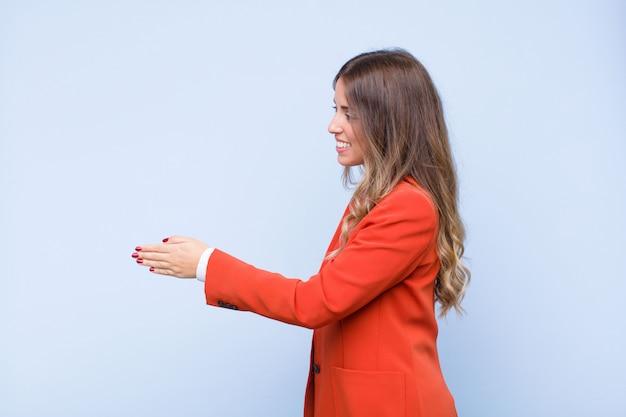 Jonge vrij spaanse vrouw die, u begroeten en een handschok glimlachen glimlachen om een succesvolle overeenkomst te sluiten