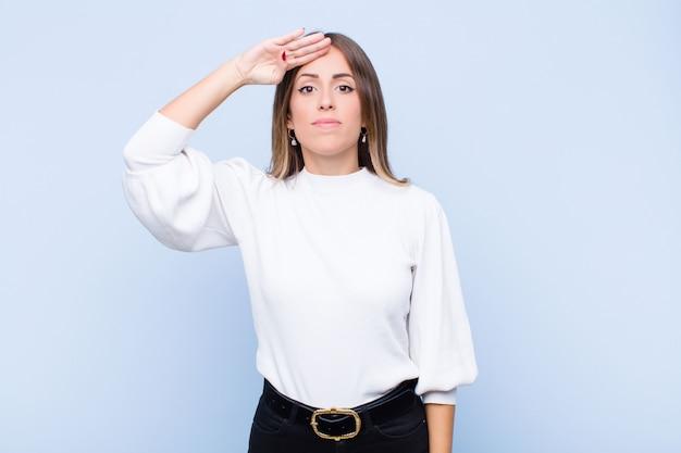 Jonge vrij spaanse vrouwengroet met een militaire begroeting in een daad van eer en patriottisme, die respect tonen tegen blauwe muur
