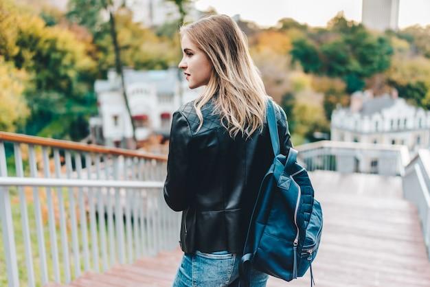 Jonge vrij terloops geklede hipster meisje toerist poseren buiten op de trappen van het stadspark met een rugzak