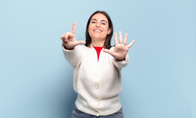 Jonge vrij toevallige en vrouw die vriendelijk glimlacht kijkt, nummer zeven of zevende met vooruit hand toont, aftellend