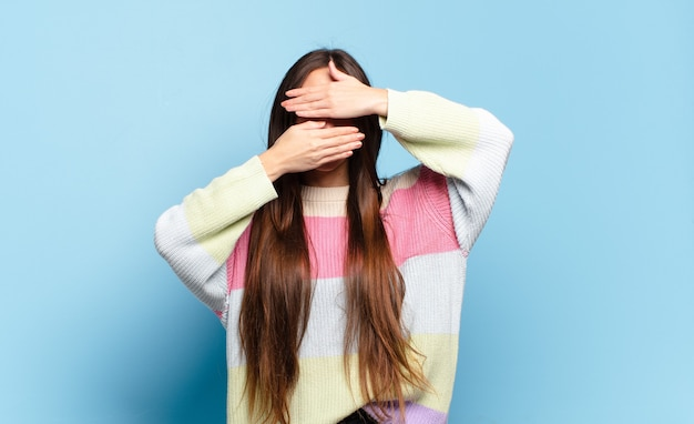 Jonge vrij toevallige vrouw die gezicht behandelt met beide handen die nee zeggen tegen de camera! afbeeldingen weigeren of foto's verbieden