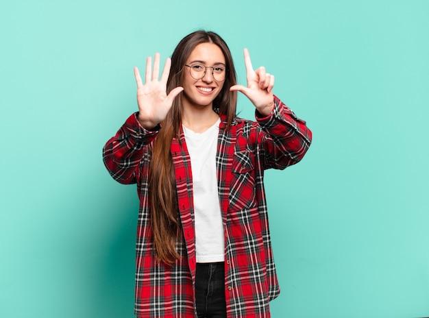 Jonge vrij toevallige vrouw die vriendelijk glimlacht kijkt, nummer zeven of zevende met vooruit hand toont, aftellend