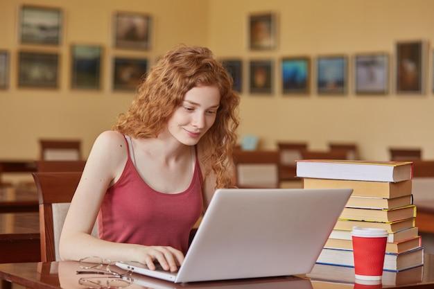 Jonge vrij vrouwelijke student met laptop en boeken die in middelbare schoolbibliotheek werken, die bij lijst zitten