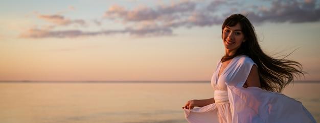 Jonge vrije vrouw die in witte kleding dichtbij de zee bij zonsondergang loopt