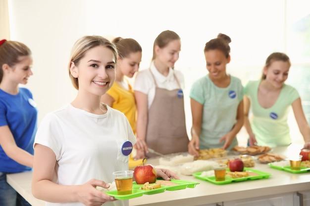 Jonge vrijwilliger en haar team in de buurt van tafel met verschillende producten binnenshuis