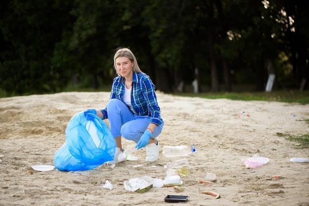Jonge vrijwilliger oppakken van plastic flessen op het strand in de buurt van het park.