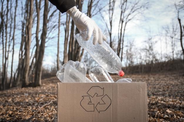 Jonge vrijwilligers die gebied in hout schoonmaken, met houd plastic fles bij openbaar park. mensen en ecologie. inzameling van plastic afval in de natuur voor recycling.