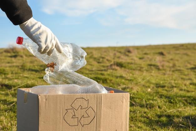 Jonge vrijwilligers die gebied in park schoonmaken, met houden plastic fles bij openbaar park. mensen en ecologie. inzameling van plastic afval in de natuur voor recycling.