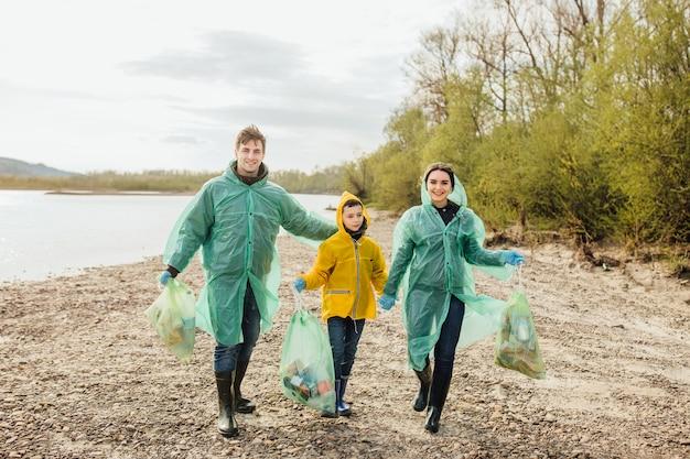 Jonge vrijwilligers met vuilniszakken. ecologie. jong gezin op de natuur.