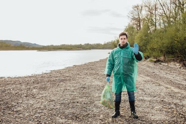 Jonge vrijwilligersmens met vuilniszakken die huisvuil in openlucht ecologieconcept schoonmaken. bij rivier.