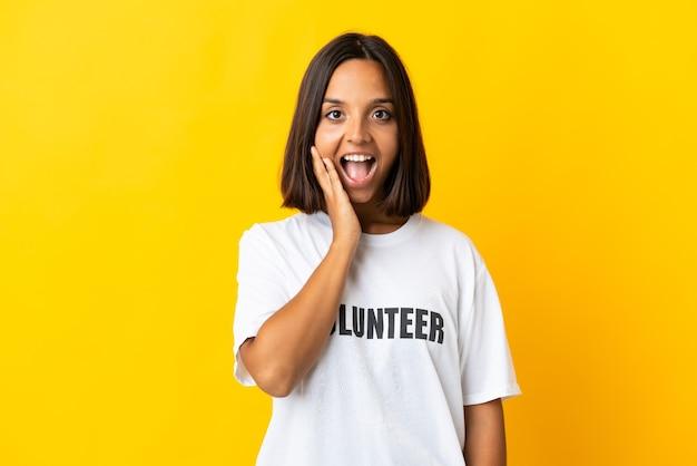 Jonge vrijwilligersvrouw die op gele achtergrond met verrassing en geschokte gezichtsuitdrukking wordt geïsoleerd