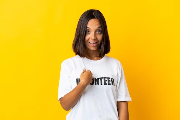 Jonge vrijwilligersvrouw die op gele muur met verrassingsgelaatsuitdrukking wordt geïsoleerd
