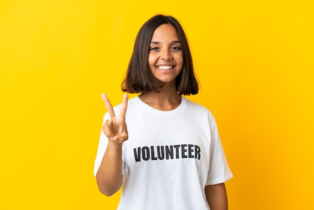 Jonge vrijwilligersvrouw geïsoleerd glimlachend en overwinningsteken tonen